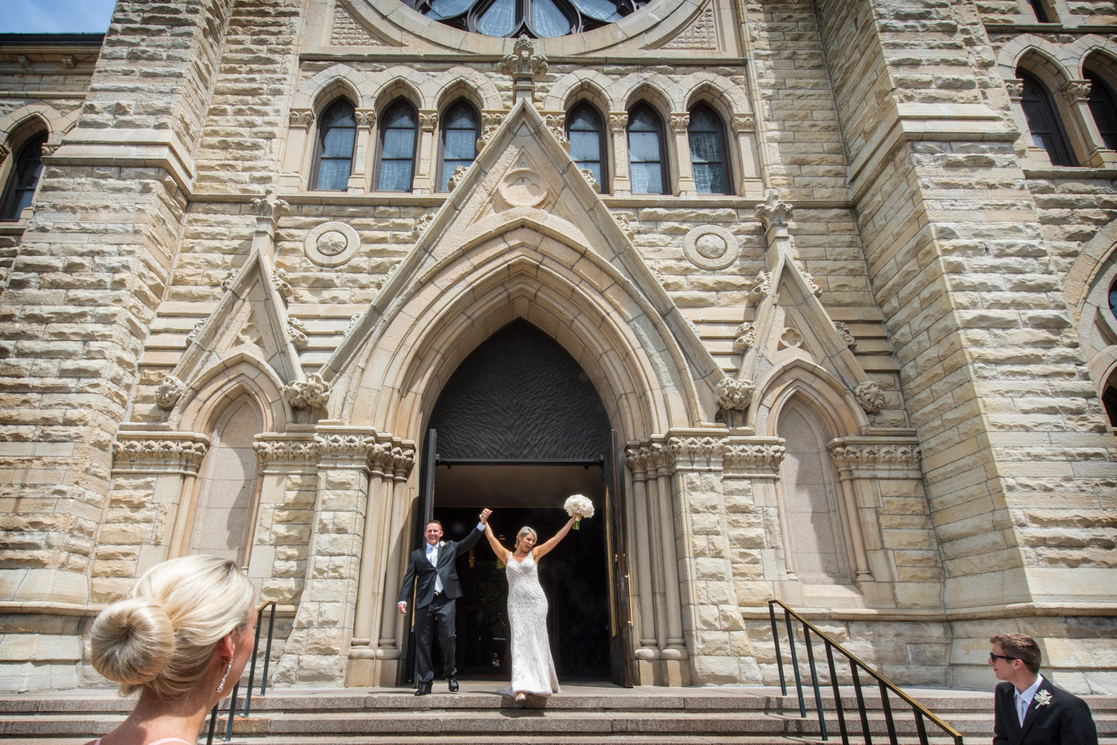 Excited bride raising bouquet outside Holy Name Cathedral after her ceremony in Chicago