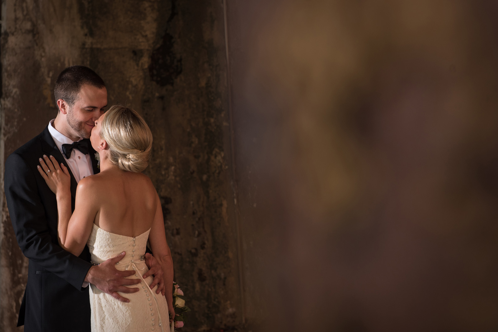 Bride and Groom kissing under viaduct