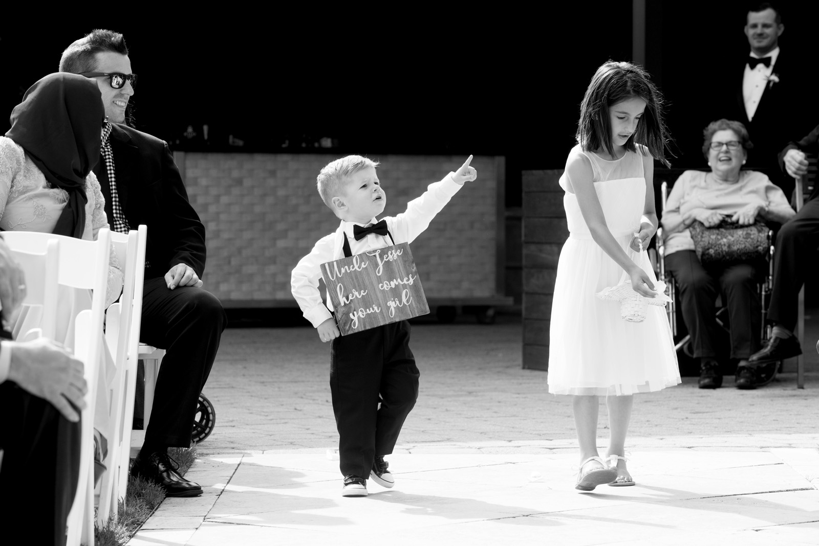 Black and White photo of Ring bearer and flower girl coming down the aisle at outdoor ceremony at Galleria Marchetti in Chicago