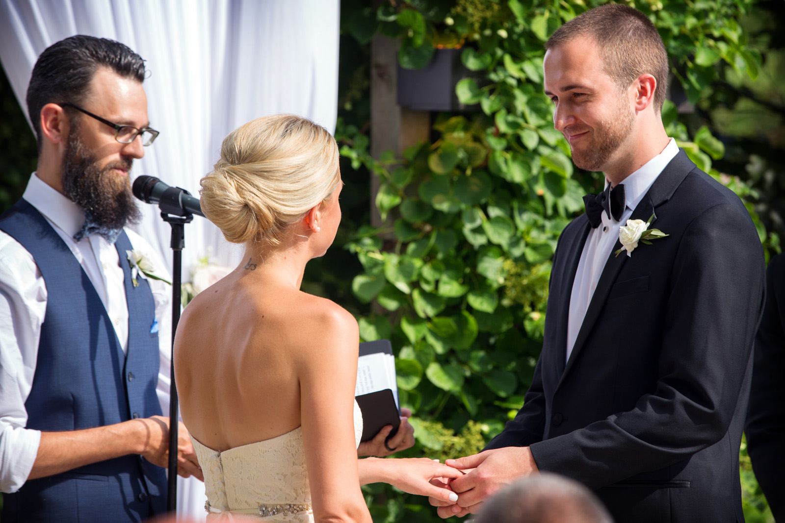 Groom placing ring on brides fingers at outdoor wedding ceremony