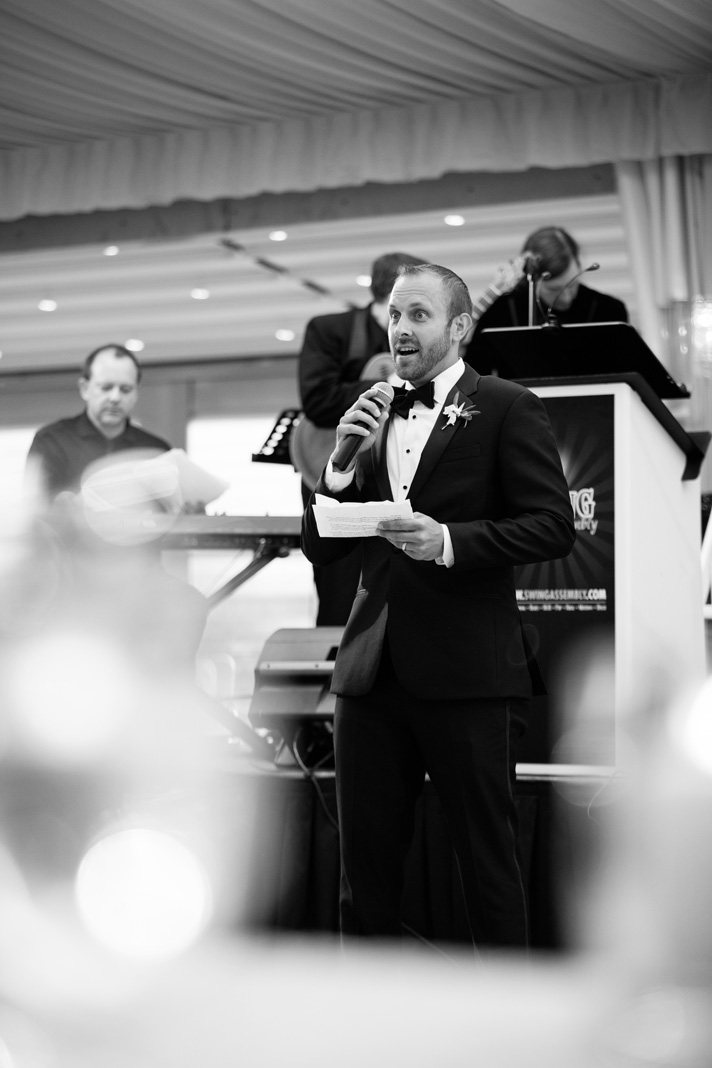 Best man delivering funny speech at wedding reception