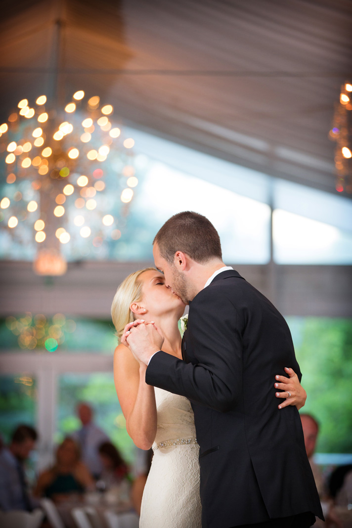 Groom kissing bride during First Dance at wedding reception