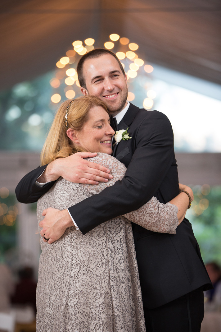 Mother of the Groom hugging her son during wedding reception dance