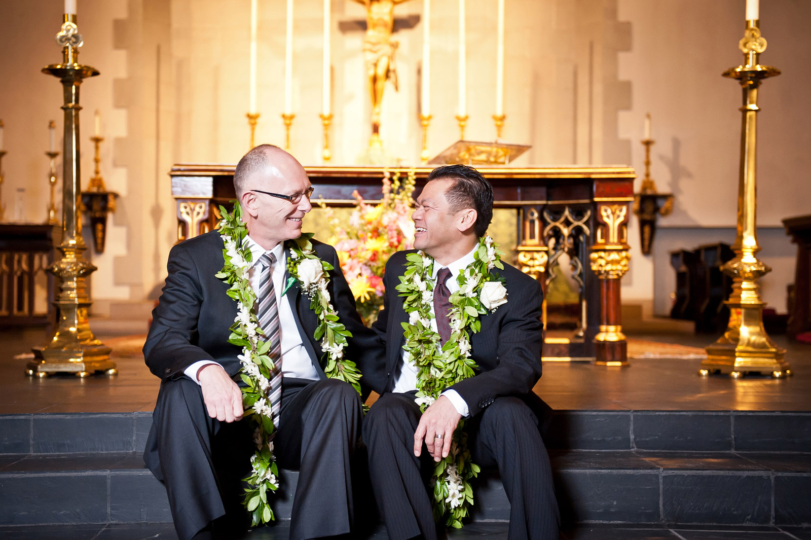 Gay marriage couple celebrate their same sex ceremony on the steps of the church altar