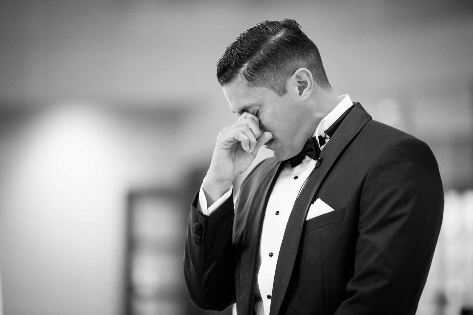 Groom gets a tear in his eye and begins to cry as he sees his wife coming down the aisle with her father