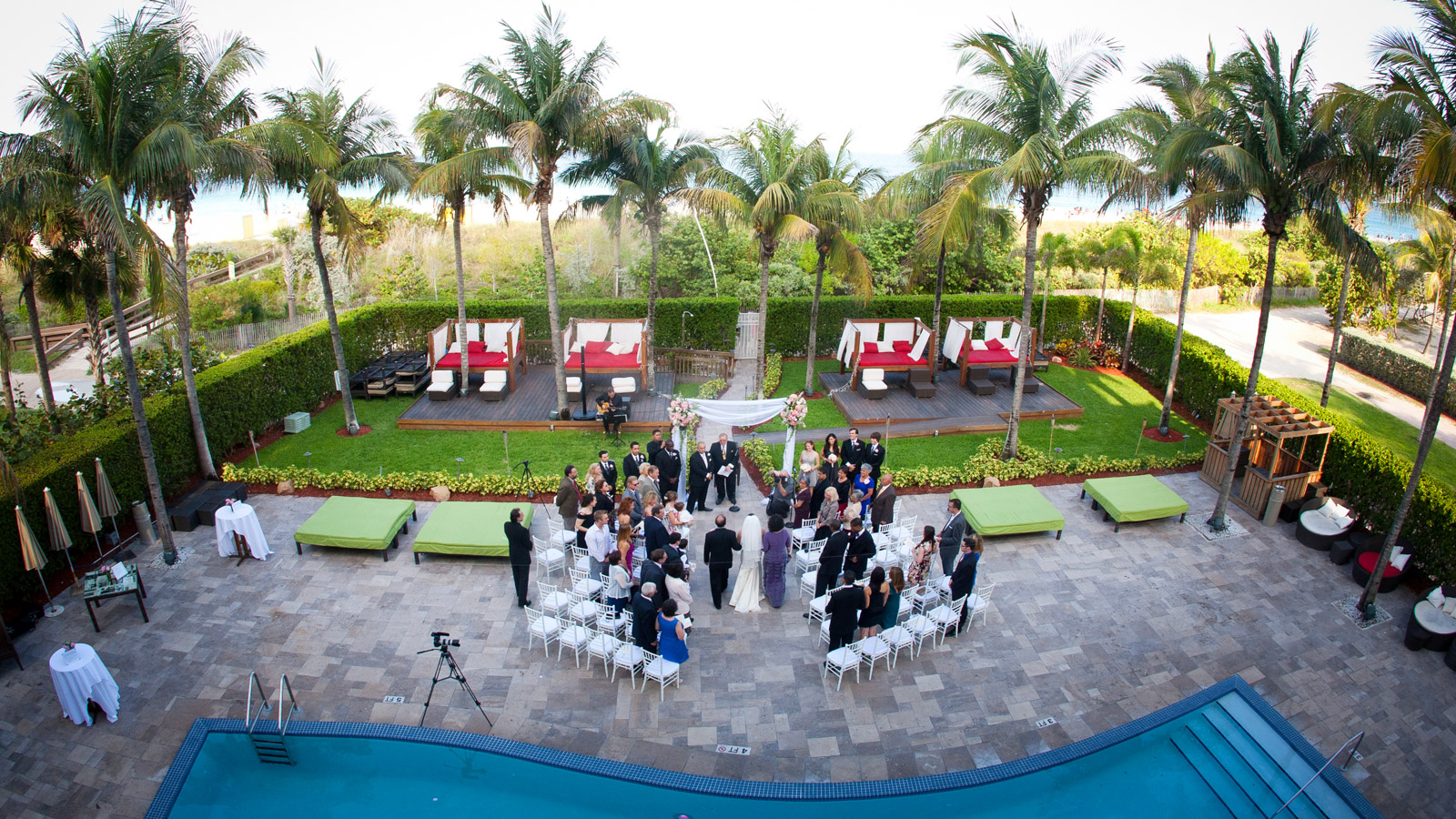 Wedding ceremony by pool under palm trees in south Miami Florida