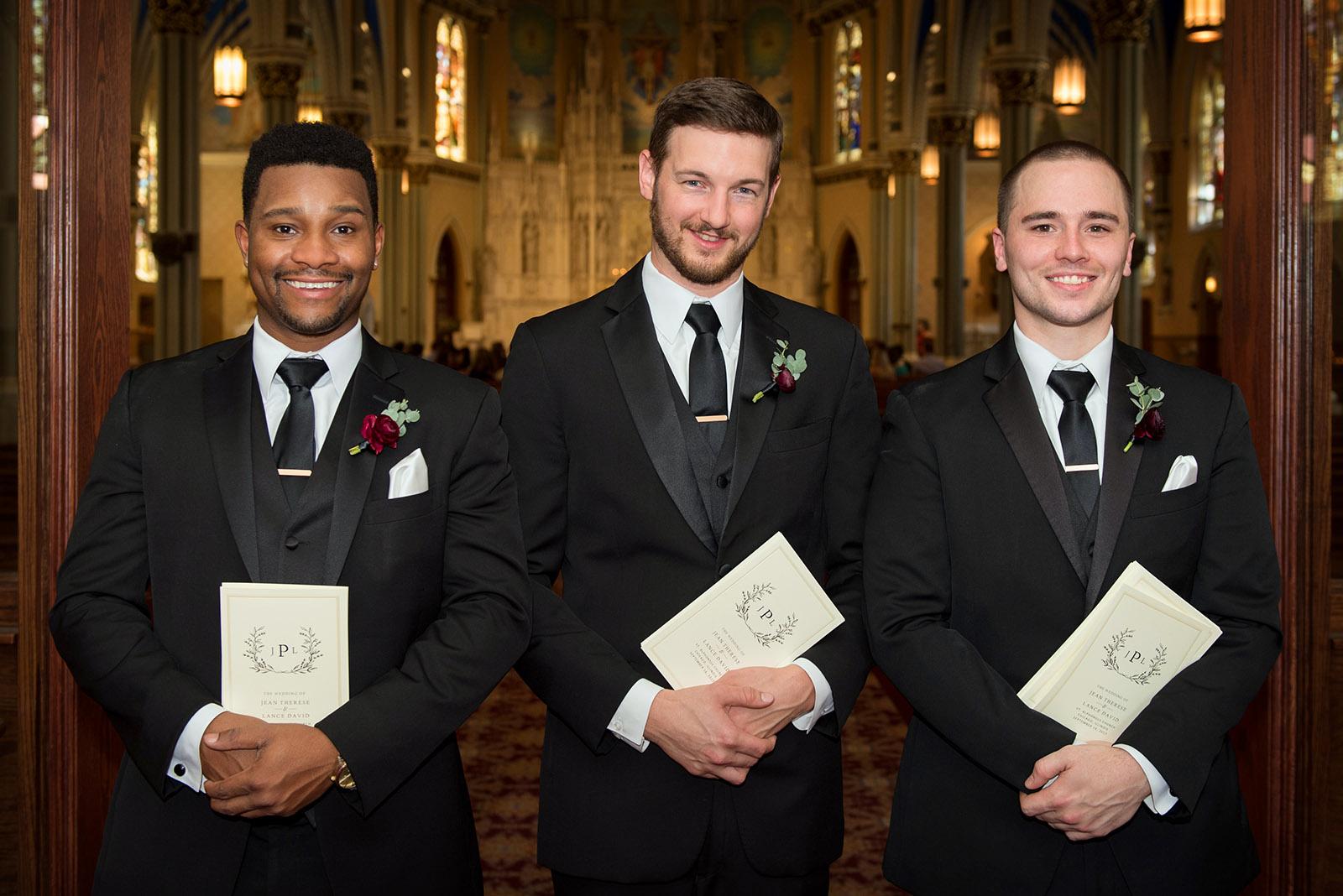 Ushers holding wedding programs