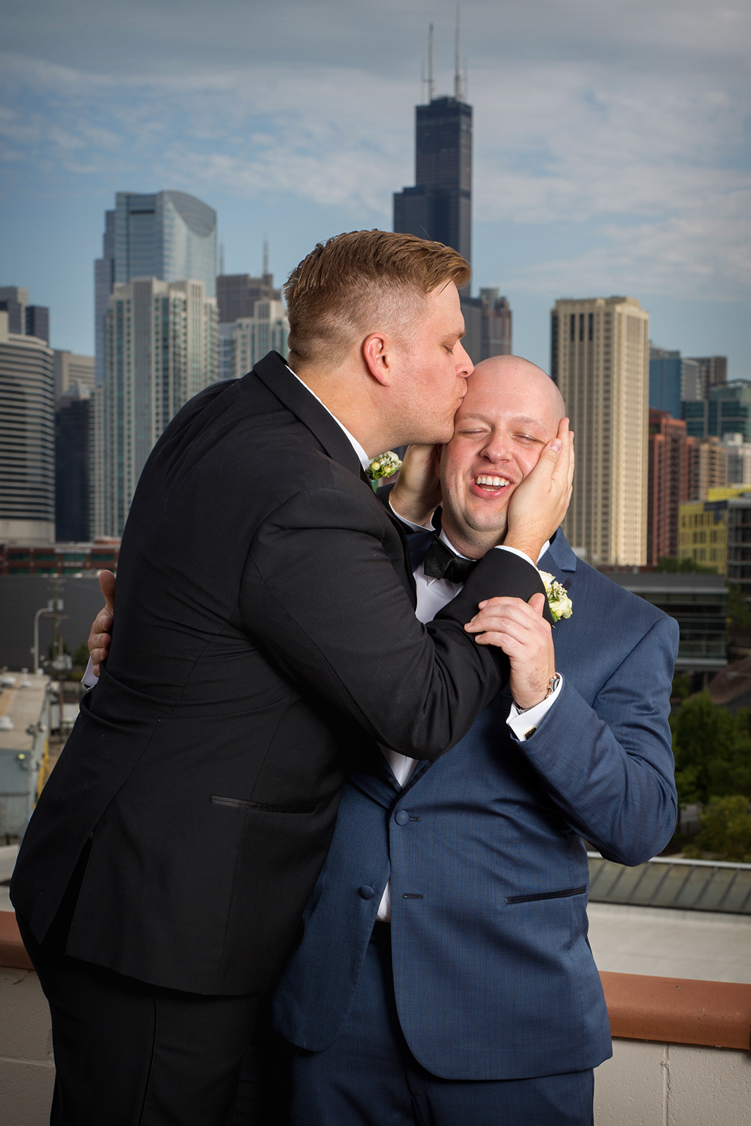 Best Man kissing groom on head