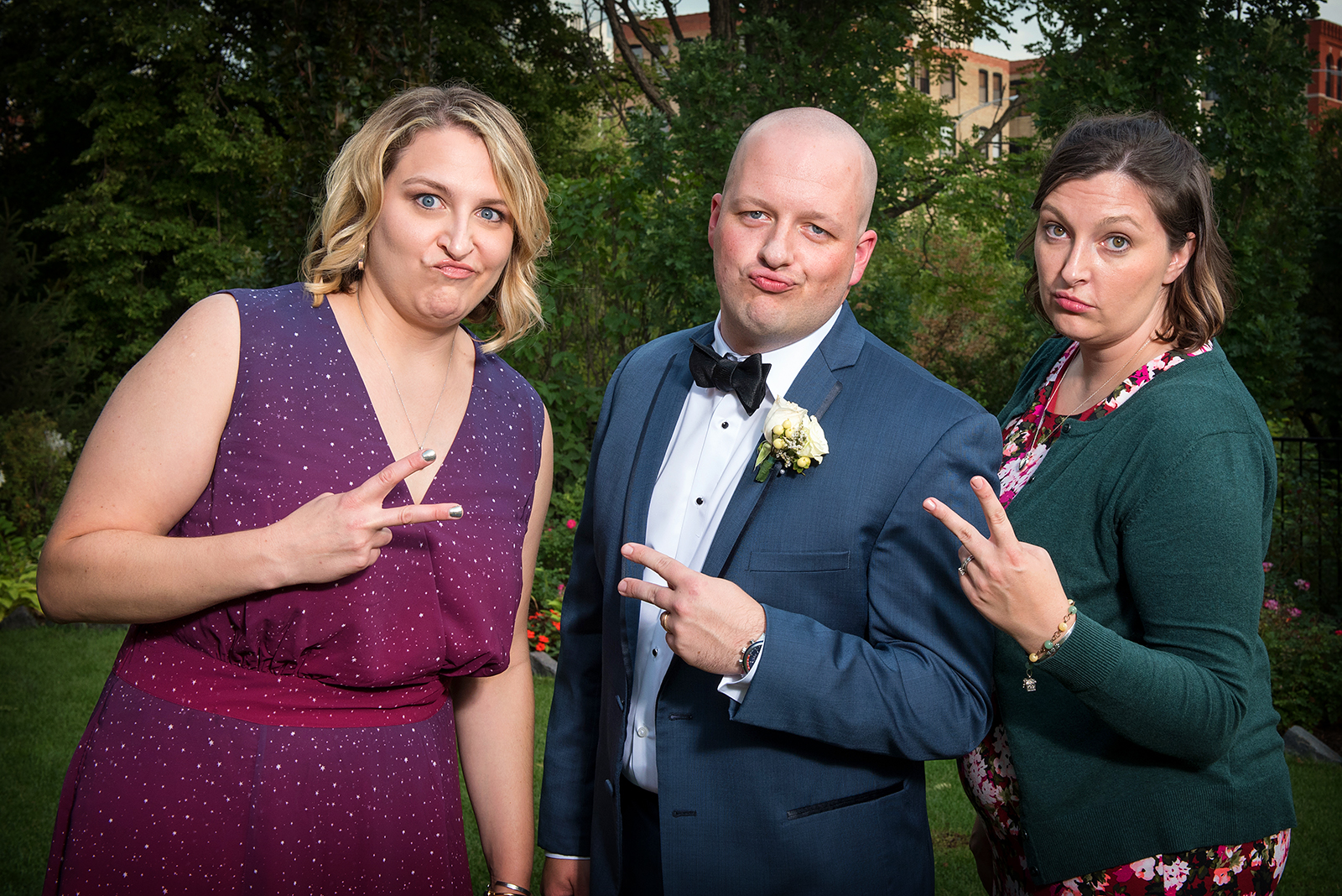 Groom with Sisters throwing signs