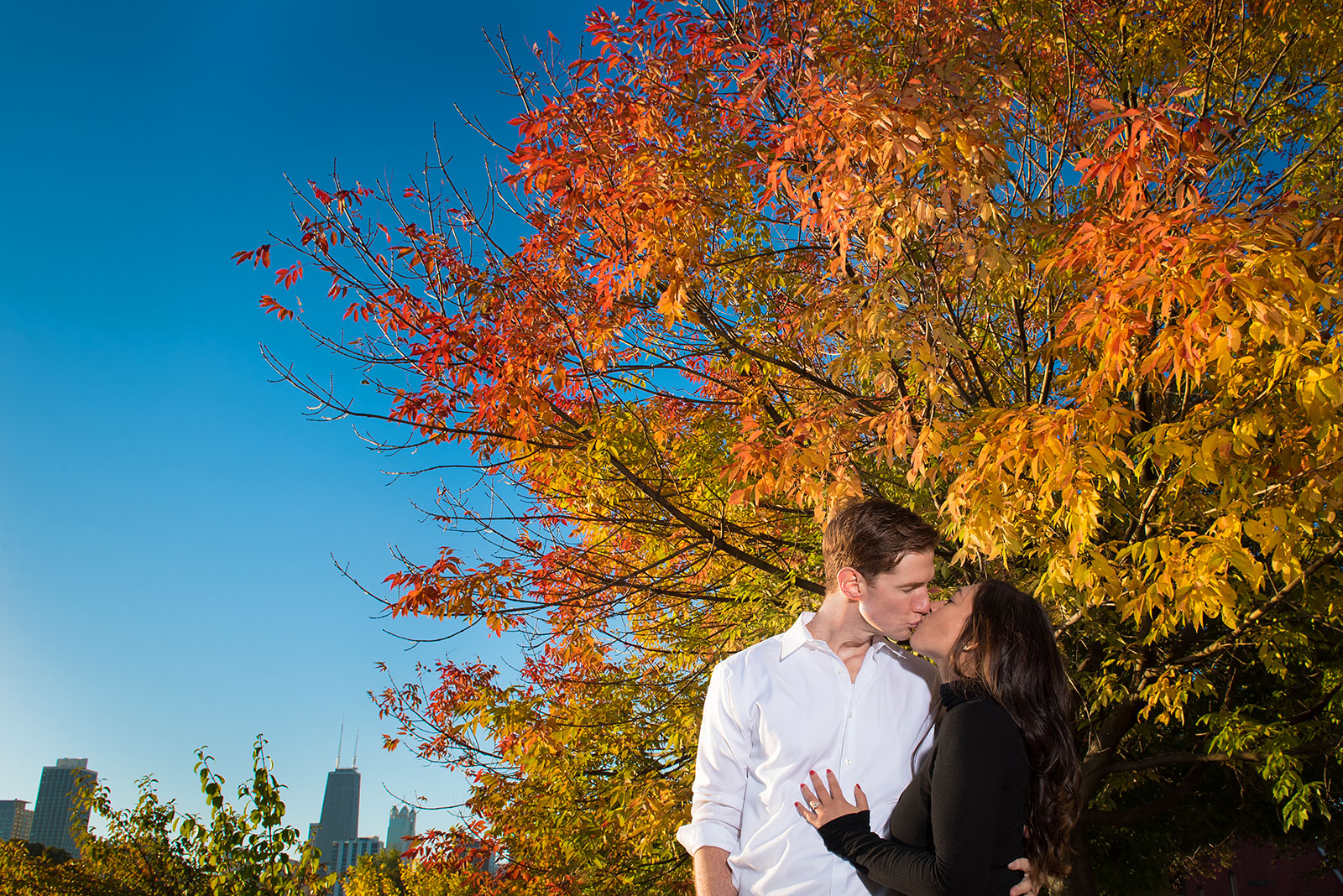 Fall Engagement Photo Couple Kissing Beneath Colorful Tree