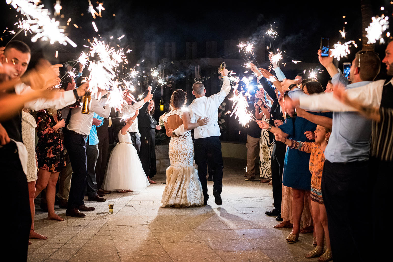 Newlyweds exit wedding reception guests sparklers