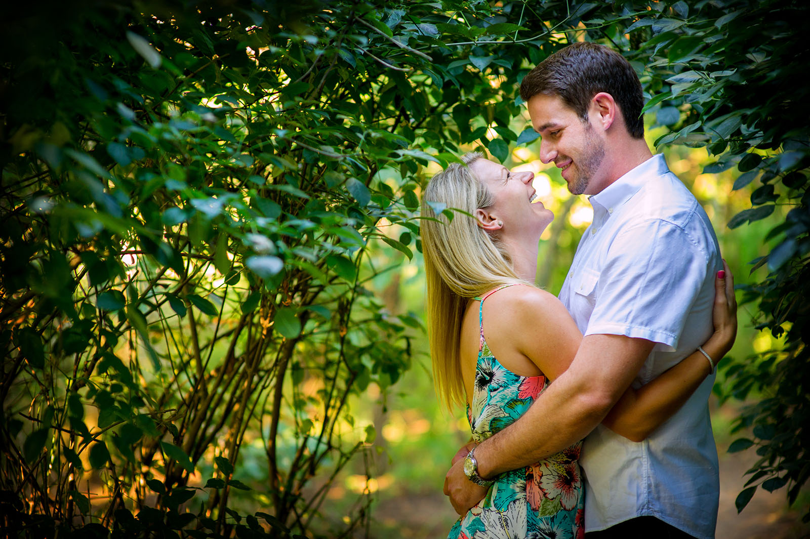 Colorful photo of couple hugging and laughing under a tree in Spring